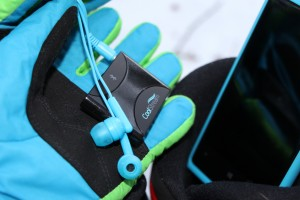 The CoolStream Duo shown with ski gloves and earbuds