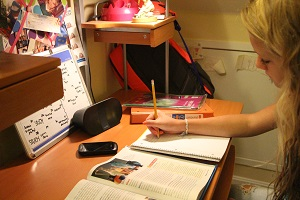 Beautiful girl studying at her desk with a CoolStream Bluetooth Portable Speaker.